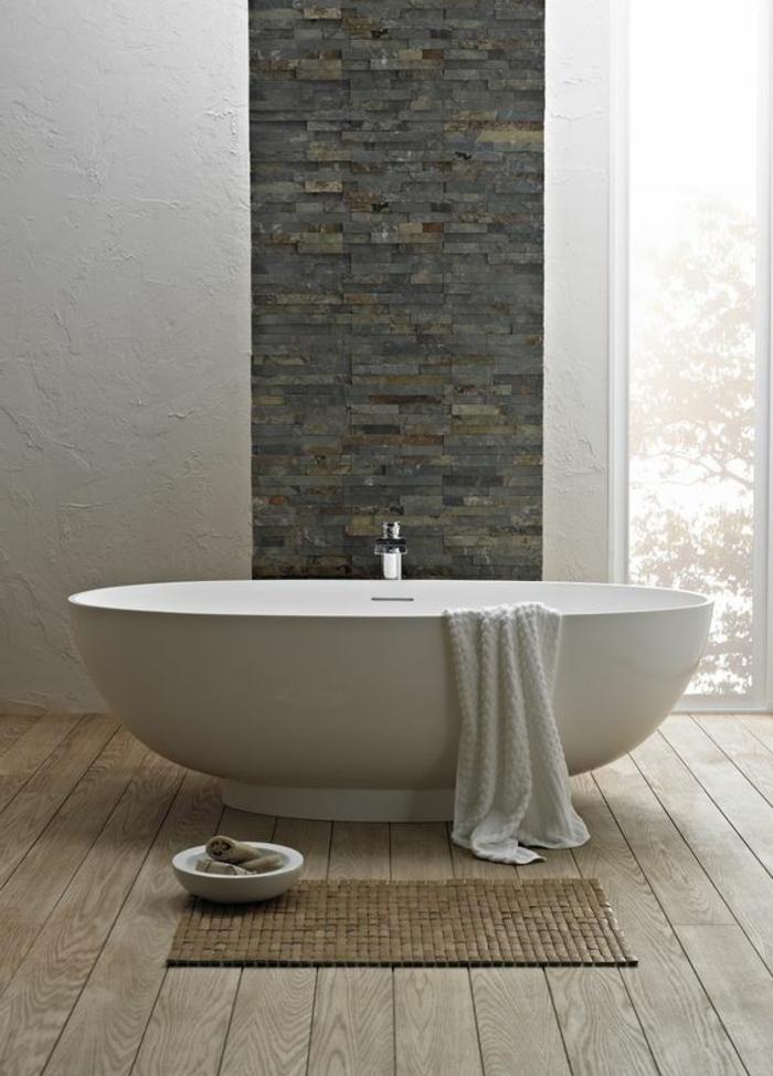 ambiance salle de bain, salle d'eau simple et belle, baignoire ovale, parement mural pierres et enduit blanc
