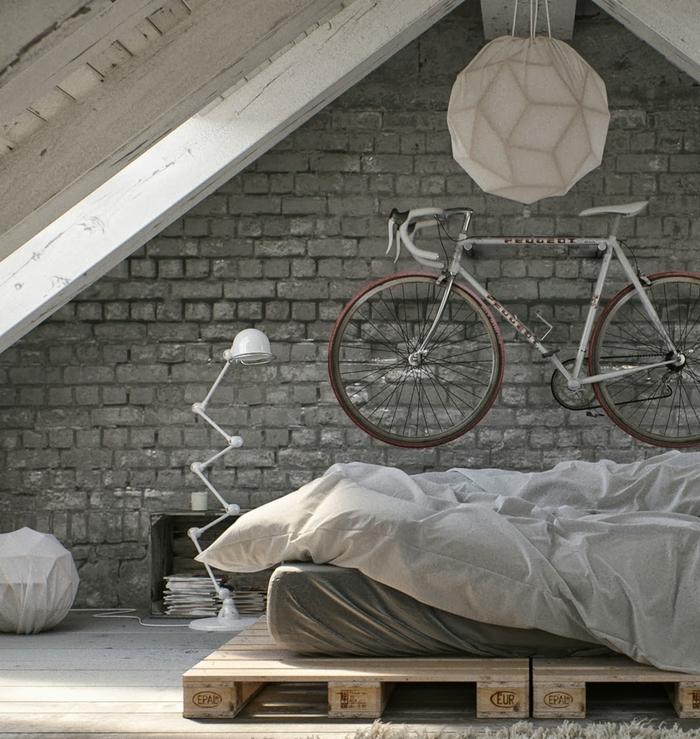 idée originale pour un aménagement sous pente, ambiance industrielle et loft avec un mur en briques grises et un lit palette europe