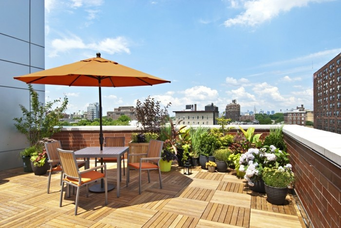 idée pour aménager sa terrasse sur le toit d un bâtiment, revêtement en bois, table et chaises grises, plantes dans des pots de fleurs gris, parasol orange