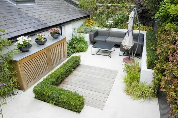 idee salon de jardin, canapé et table gris sur une terrasse zen, revêtement bois, carrelage, parasol, buis, arbustes et arbres, gravier en bordures