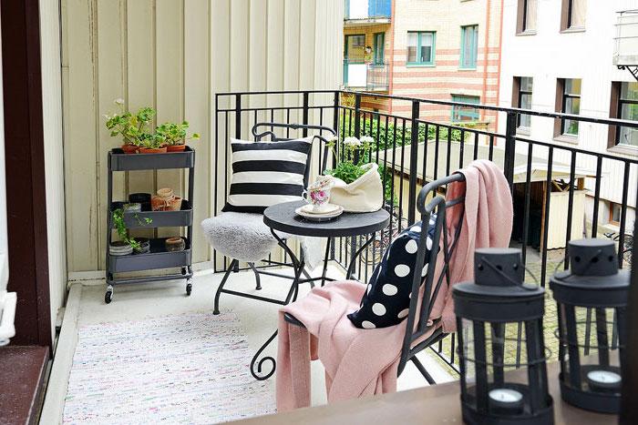 aménager une terrasse avec balustrade noire, tapis cocon, chaises et table metallique noire, étagère fleurs, lanternes noires