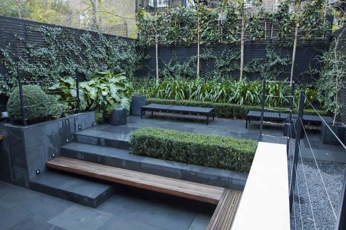 aménager sa terrasse, revêtement gris, zone de gravier gris, banc noirs, buis et arbustes, plantes grimpantes sur une clôture