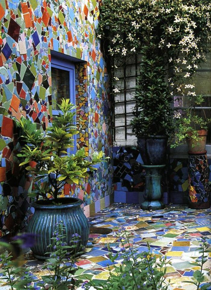 idee de parterre de fleur avec sol et mur en mosaique bleue et verte et des grands pots avec des petits arbres