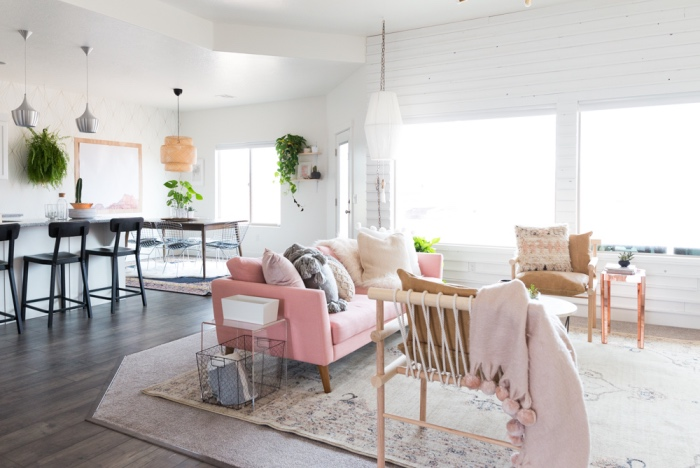 cuisine ouverte sur salon avec idee deco cocooning, tapis oriental usé, canapé rose, chaises en bois, lambris blanc, suspensions originales