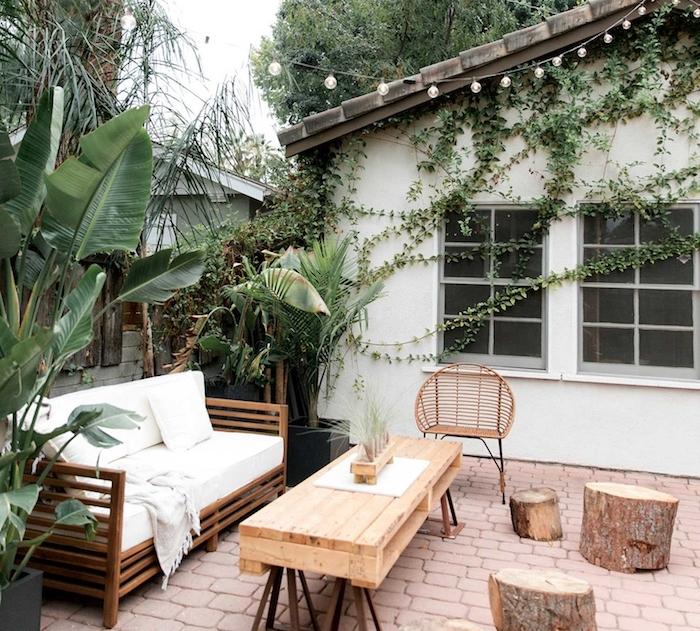 deco terrasse exterieure, carrelage terre cuite, table palette avec pieds en metal canapé en bois, bûches de bois en tabourets, plantes vertes exotiques