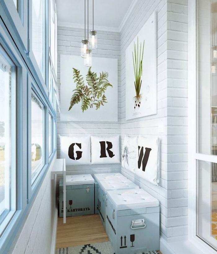 deco terrasse blanche, canapé en coffres bleus avec des assises blanches, coussins blancs avec des lettres noires, deco murale de panneau blancs, dessin de plantes vertes, revêtement bois, tapis gris à motifs noirs, suspensions industrielles