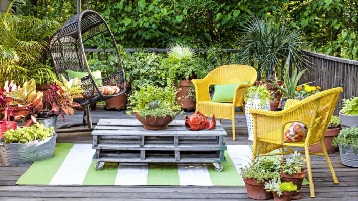 amenagement terrasse exterieure, revêtement bois, tapis blanc et vert, table en palette à roulettes, chaises jaunes, balançoire suspendu, plusieurs plantes exotiques dans pots de fleurs