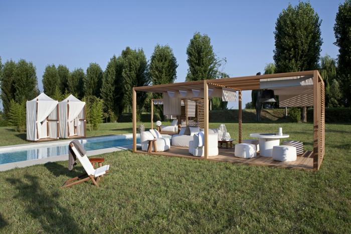deco terrasse exterieure sur un gazon vert, pergola bois, chaise longue, canapé, table et fauteuils blancs, bassin aquatique