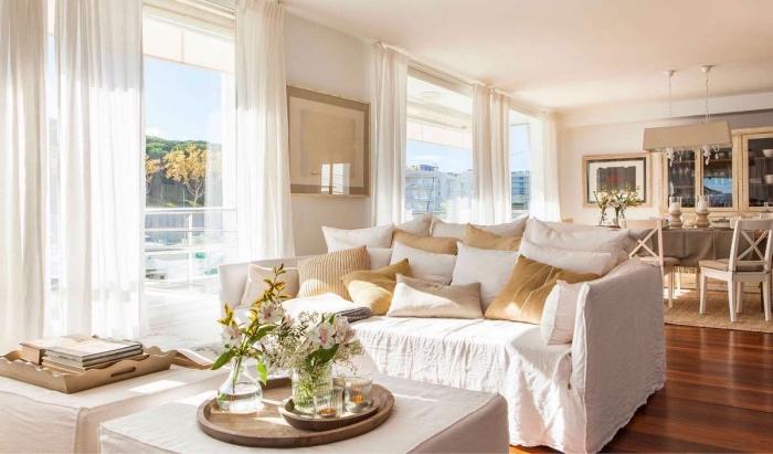 salle à manger ouverte sur un salon blanc et beige avec canapé blanc et coussins blanc et beige, tables basses blanches, revêtus de tissu, deco de bouquets