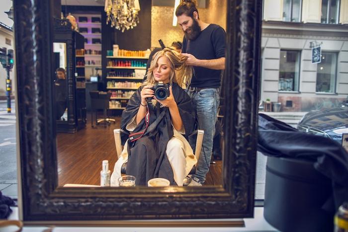 meche blonde, femme devant grand miroir, soins de beauté cheveux, visite salon coiffeur, lustre en verre et cristaux