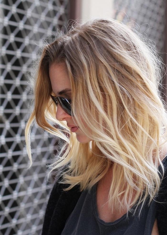 ombré hair blond, femme aux cheveux mi longs, coiffure naturelle avec volume, cheveux messy en châtain clair avec pointes blondes