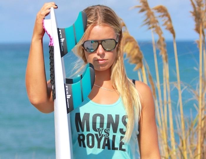 californien cheveux, débardeur bleu avec lettres noires, ongles courts peints en noir, planche de surf blanche