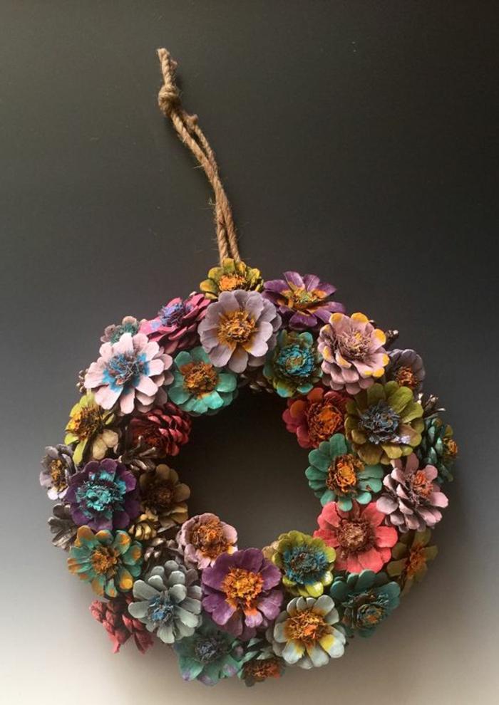 bricolage de noel facile, coueonne de cônes peints comme fleurs à accrocher à la porte