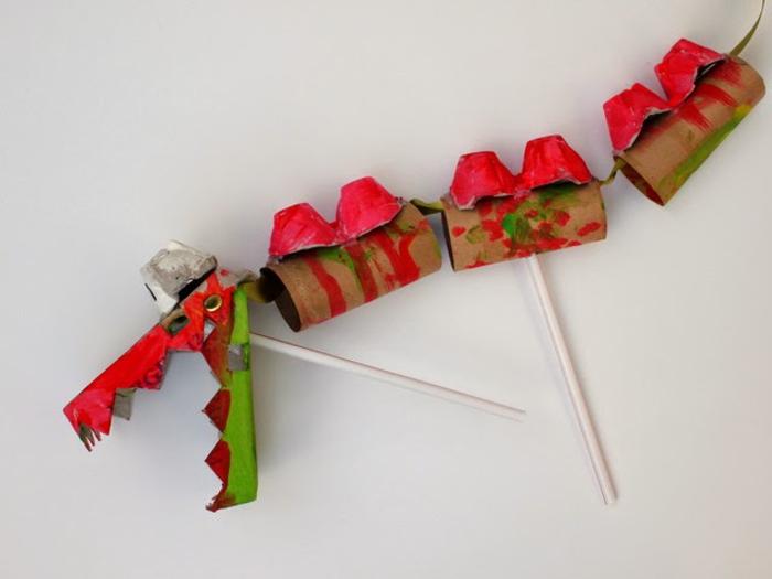 un bricolage en papier original avec des boîtes d'oeufs et des tubes en carton, comment faire un dragon chinois dansant