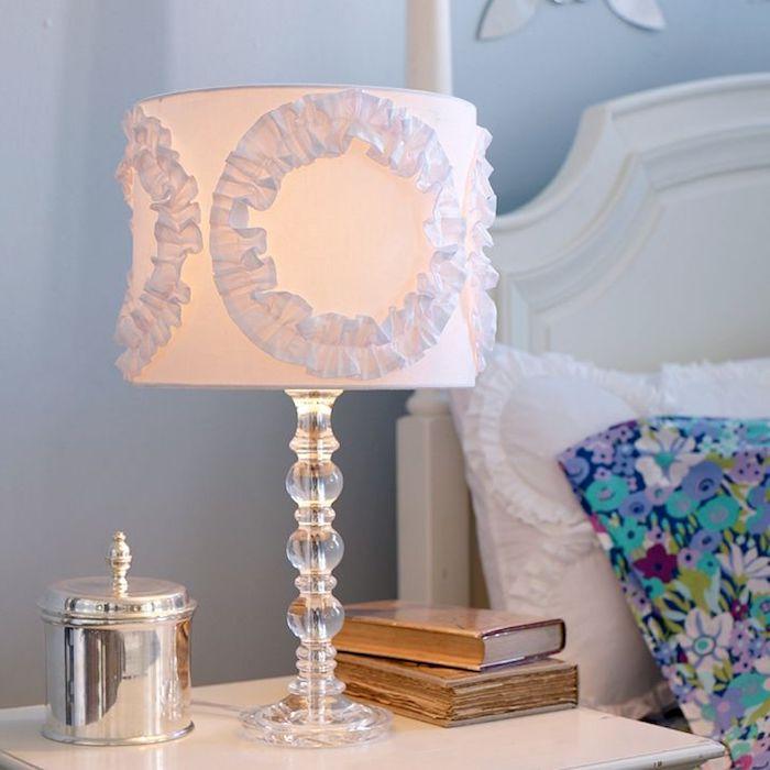 lampe de chevet, tête de lit en bois peint en blanc, coussin décoratif à motifs floraux, livres anciens avec couvertures en bois