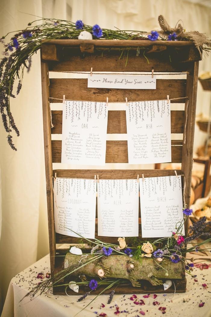 idée de decoration mariage champetre, deco cagette bois avec petites listes des invités par table et décoration de fleurs champêtres, bûche de bois