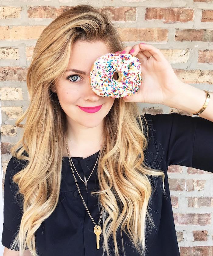 balayage sur cheveux chatain, fille et donut multicolore, ongles courts à base rose, coupe de cheveux longs