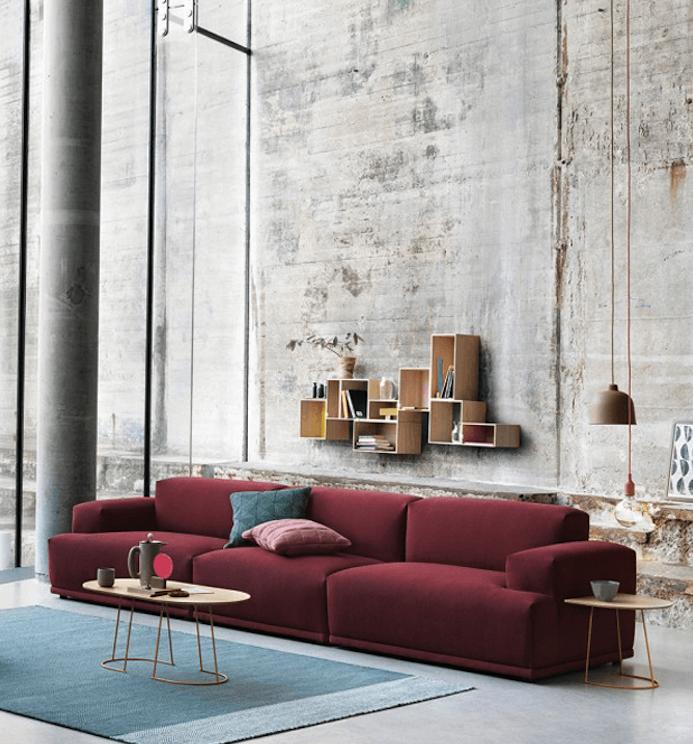 canapé couleur bordeau, mur défraichi dans un salon style industriel, tapis bleu, étagères en bois, suspensions originales