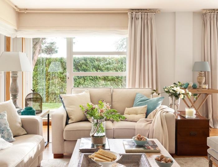 rideaux et canapés beiges, sur un fond de mur couleur blanc, table basse en bis, coussins beiges et bleus, ambiance campagne chic