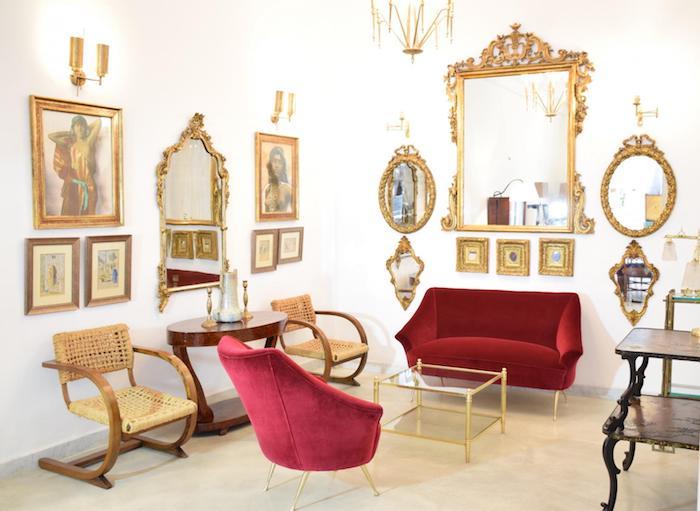 salon baroque avec fauteuil et canapé rouge, miroirs et cadres dorés, mobilier vintage en bois, deco luxueuse