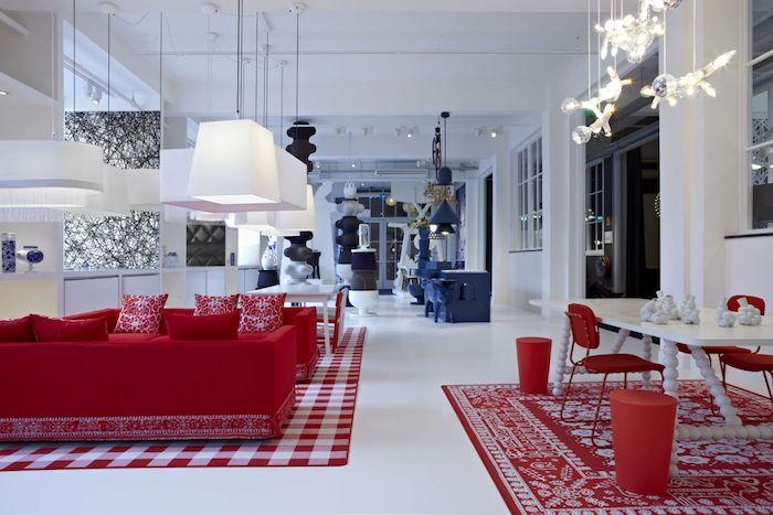 canapé rouge design dans un salon ouverte sur une cuisine, salle à manger, murs et sol blancs, coin repas bleu, suspensions originales