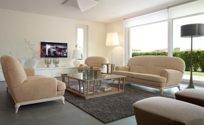 idée amenagement salon blanc et beige, canapé et fauteuils ecru, revêtement sol et tapis gris, tabourets marron, couleur mur blanc