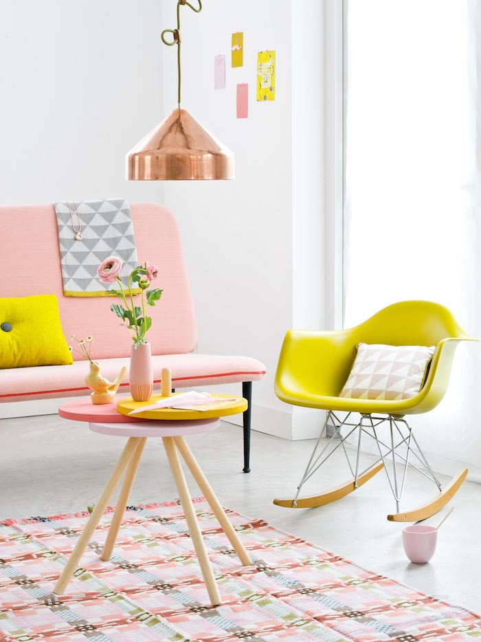 intérieur aux couleurs vibrantes, chaise basculante en jaune avec coussin à motifs triangulaires en blanc et rose