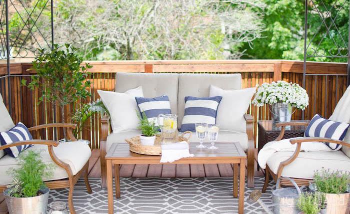 idee salon de jardin en bois composite avec canapé, fauteuils et tables en bois, coussins d assise blanc et gris, coussins décoratifs gris, bleu blanc, plantes vertes
