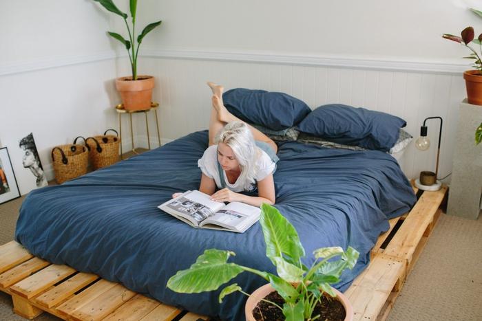 une chambre à coucher bohème chic avec lit palette à cadre assez large pour servir d'espace de rangement