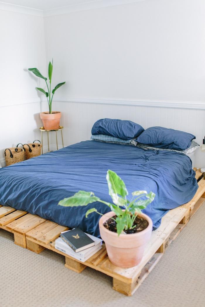 une ambiance intime et naturelle dans une chambre à coucher bohème chic à déco minimaliste de lit palette europe et des paniers de rangement en rotin