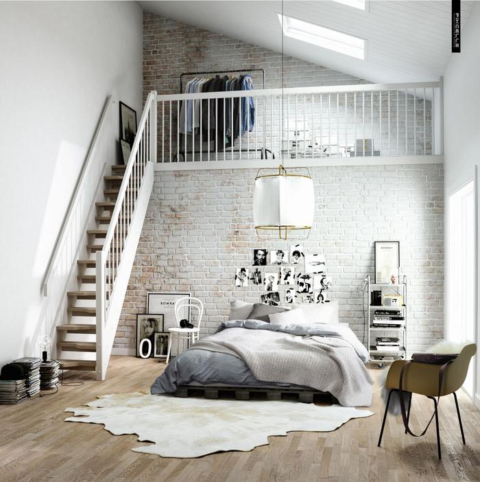 une chambre à coucher d'esprit loft tout en blanc équipée d'un lit en palette posé contré un mut en briques