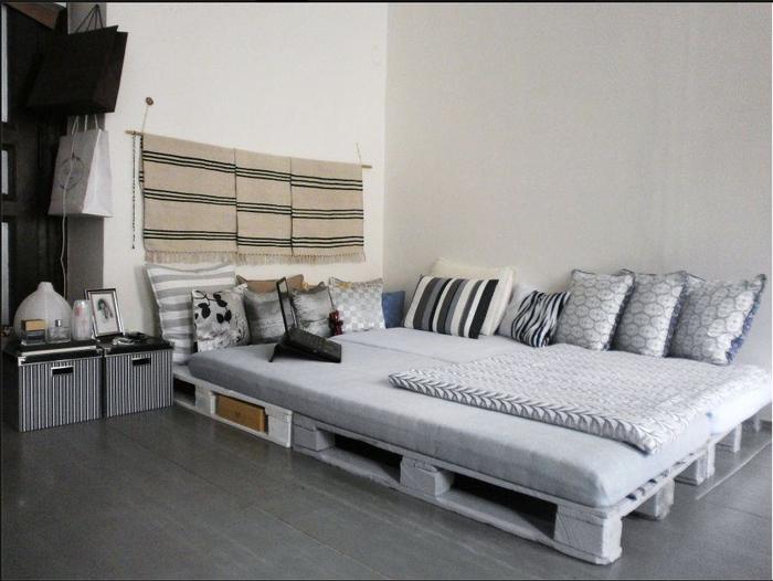 une chambre à coucher en gris et blanc de style ethnique chic avec un sommier en palette