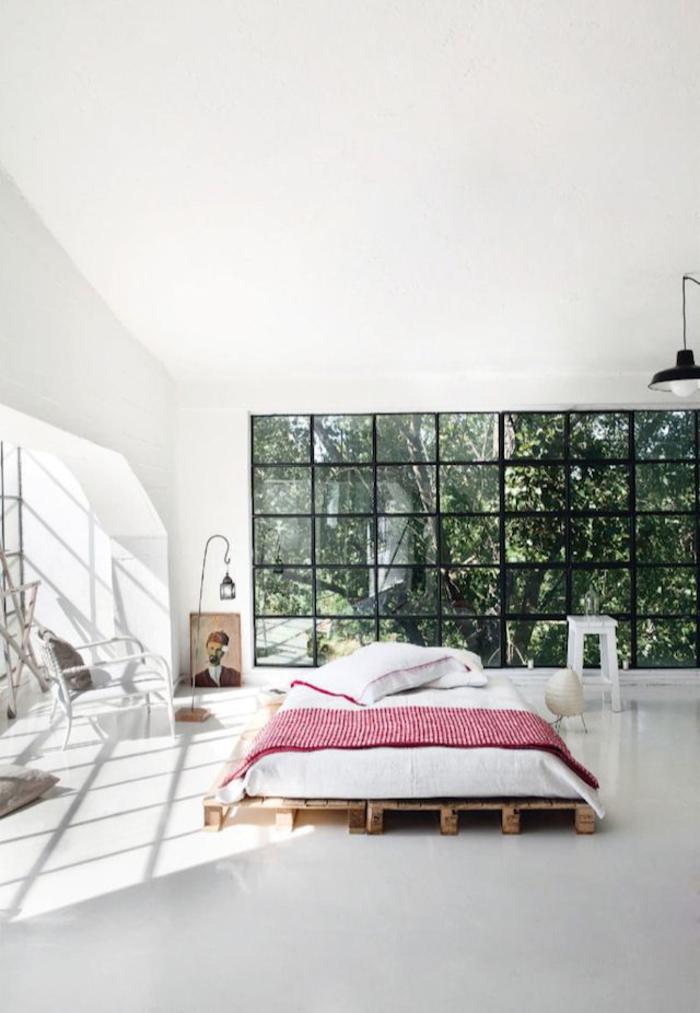 une chambre à coucher industrielle d'esprit loft avec un grand lit palette bois naturel et assez d'espace pour une circulation fluide