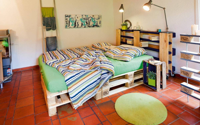 un sommier en palette et une tête de lit assortie en bois recyclé servant aussi d étagère