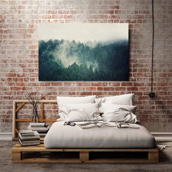 chambre à coucher de style industriel avec un mur en briques et un lit palette europe
