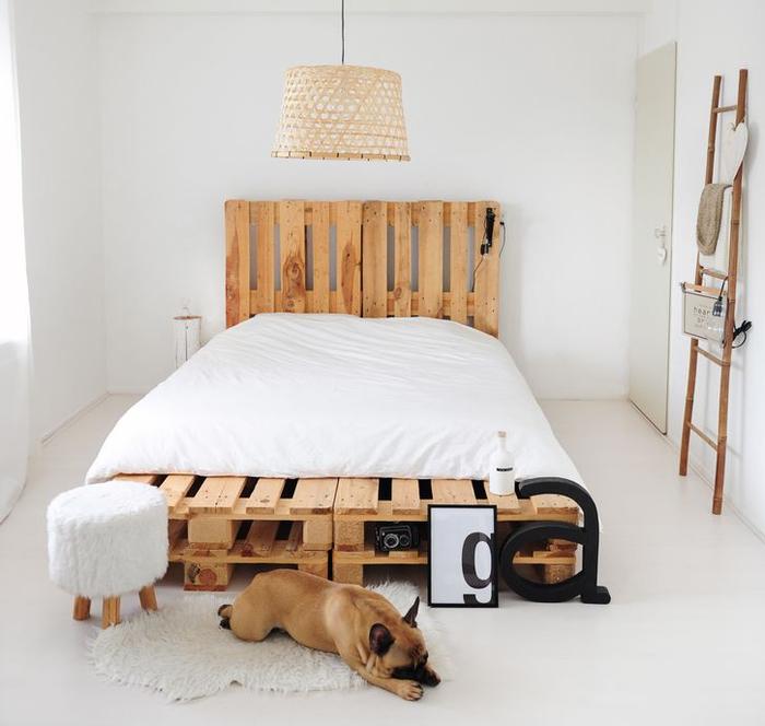 une chambre à coucher scandinave en blanc et bois naturel avec un lit en palette king size et sa tête assortie