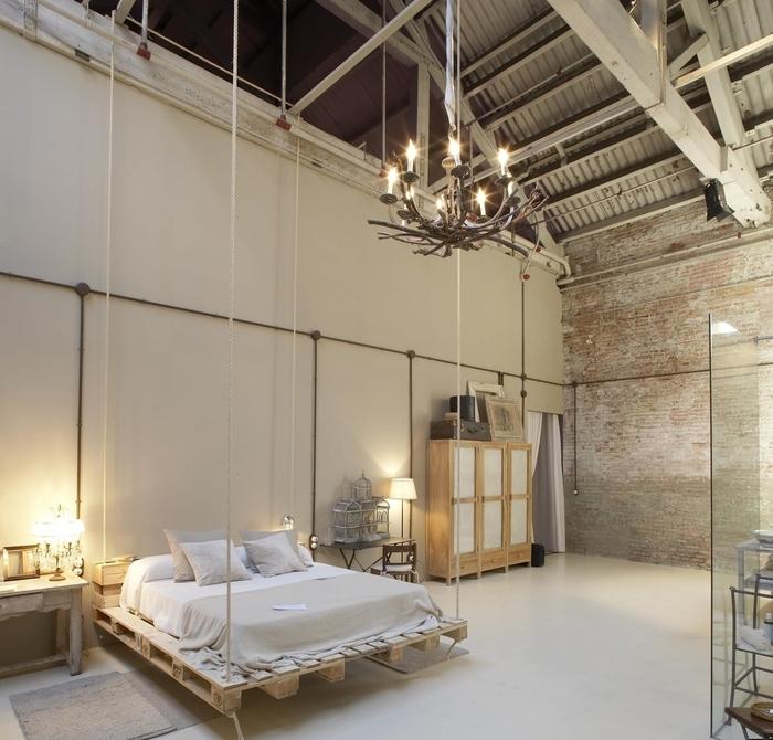 une chambre à coucher de style industriel d esprit loft avec un lit palette europe en suspensions