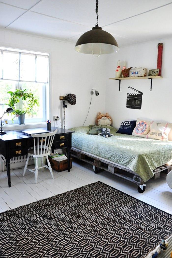 une chambre d'ado scandinave en noir et blanc avec un sommier en palette avec roulettes, joli contraste entre le parquet en bois blanc et le tapis graphique
