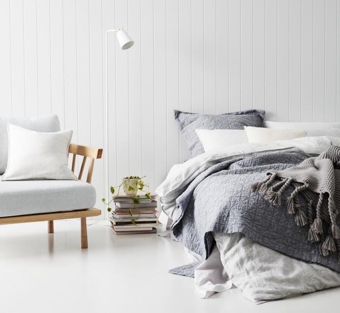 modele de chambre adulte cocooning revêtement sol et murs blanc, fauteuil en bois avec coussin d assise blanc, linge de lit blanc et gris, pile de livres