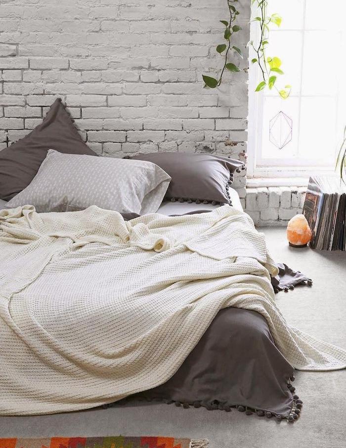 modele de chambre cocooning, mur en briques, lit matelas avec linge de lit blanc et gris, plantes vertes et magazines par terre