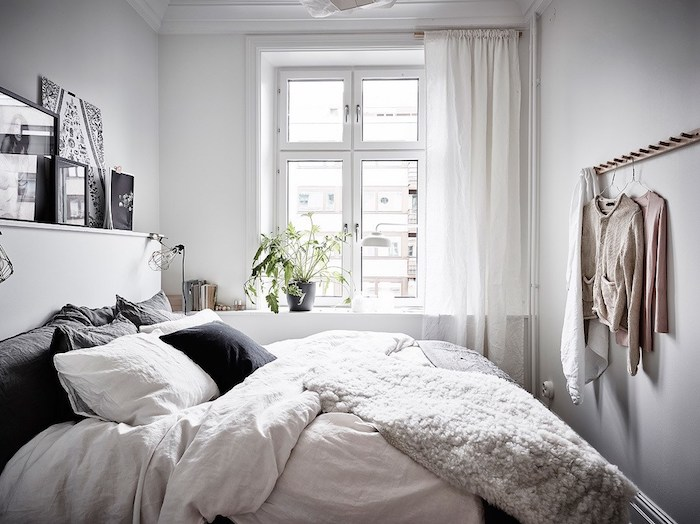 coussin scandinave, plusieurs coussins blancs et gris sur un lit avec linge de lit blanc, couverture moelleuse, decoration murale en art graphique