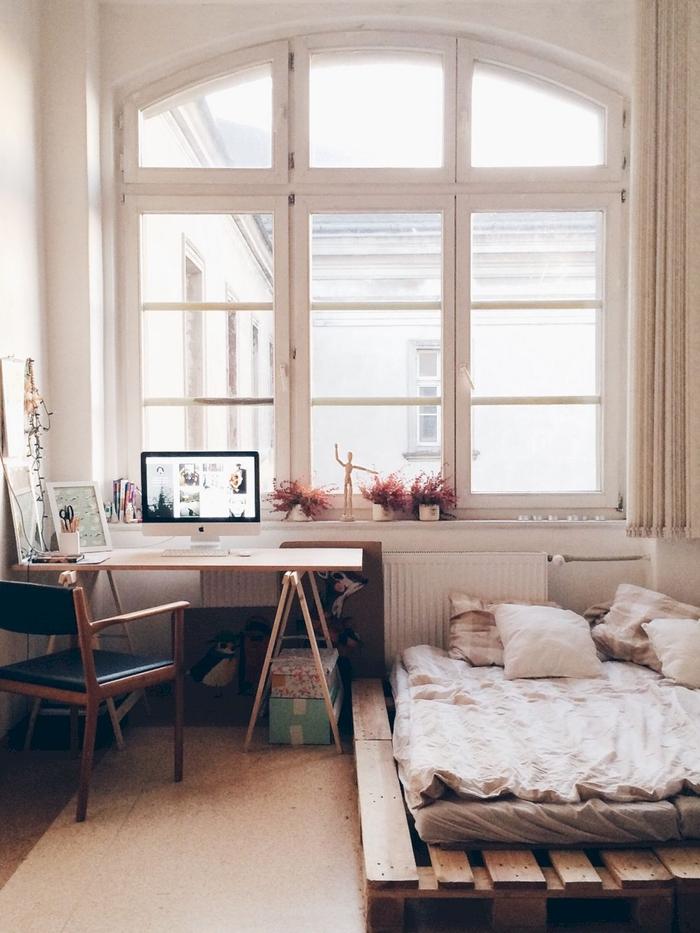 aménagement intelligent d une chambre à coucher avec espace bureau et un lit palette bois placé au ras du sol