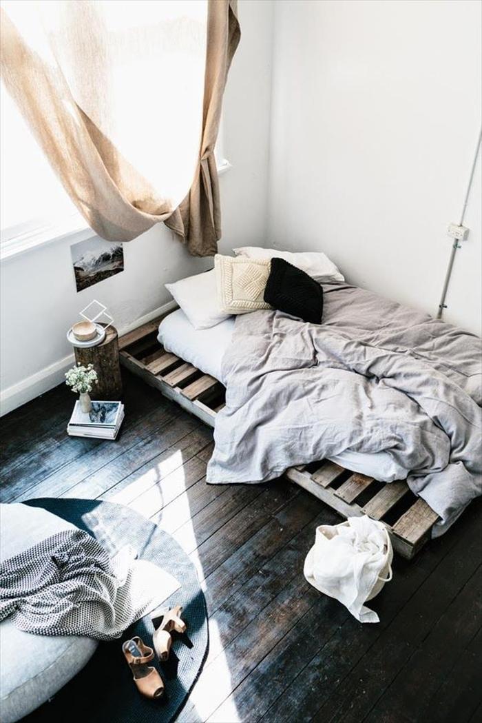une chambre à coucher d'esprit récup avec un lit palette et une table de chevet en rondin de bois