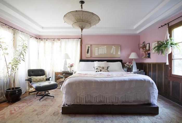 decoration interieur, lustre motifs ethnique en beige, pot à fleur noir avec plante verte, murs peints en rose avec revêtement en bois