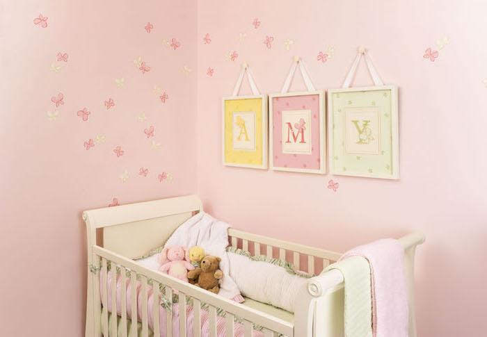 pièce aux murs rose avec décoration en papillon miniatures, serviette rose pastel sur lit bébé blanc