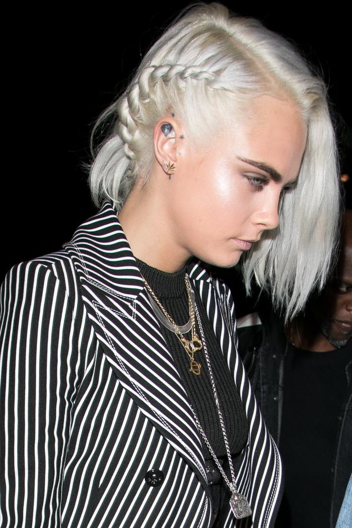 une coiffure avec tresse collée sur le côté associée à une coloration blond polaire