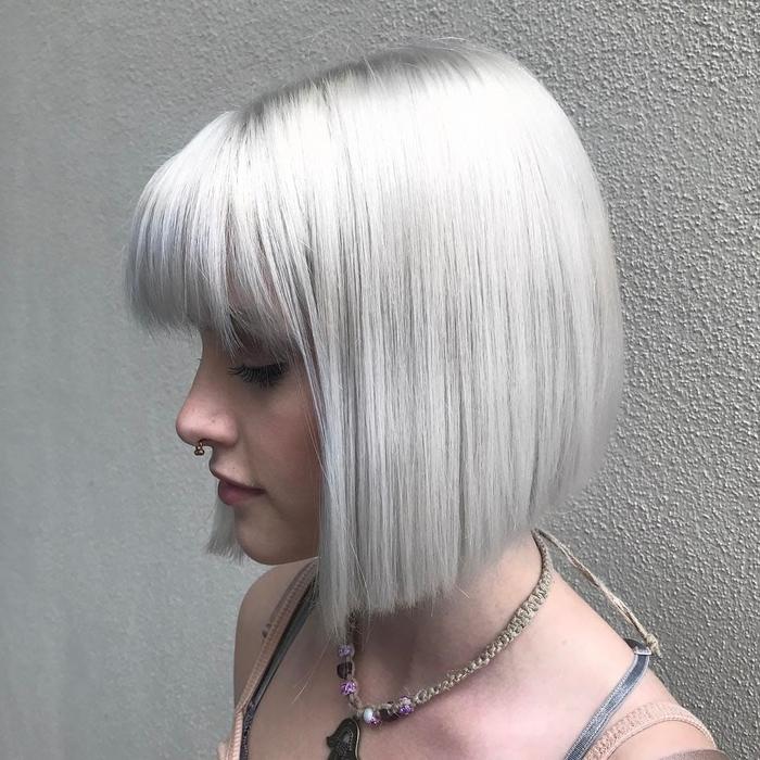 une coupe courte lisse avec frange associée à une coloration ultra tendance en blond platine