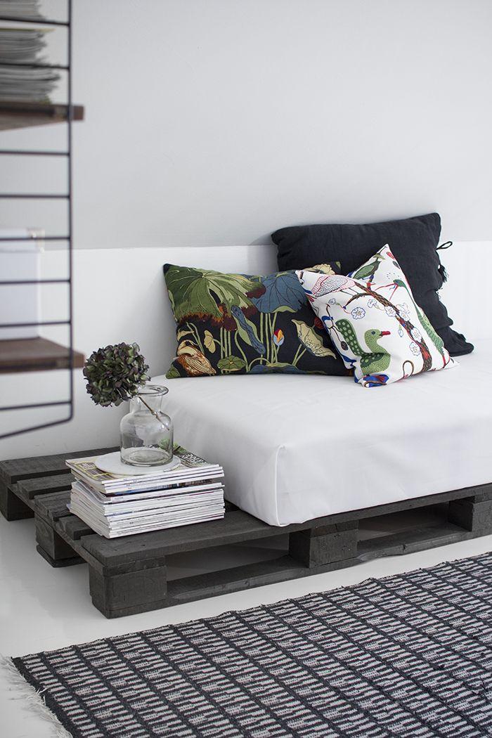 canapé en palette repeint en gris en jolie contraste avec le matelas blanc et les coussins imrpimés déparéillés