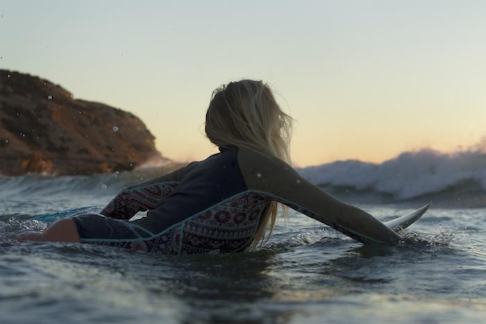 balayage blond, fille de surf qui prend la vague, costume de surf noir avec manches kaki et déco à motifs ethniques