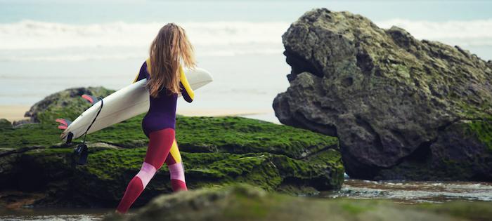 balayage californien brune, costume de surf avec legging rouge et rose et top jaune violet, planche de surf blanche